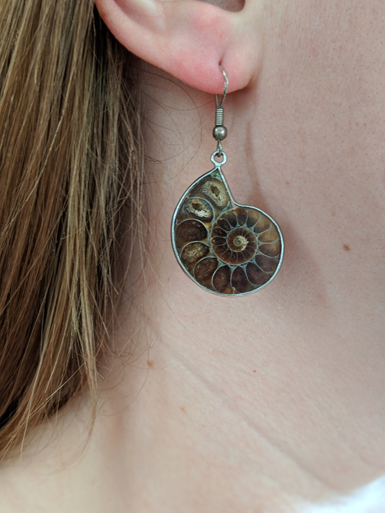 ear wearing an ammonite fossil earring